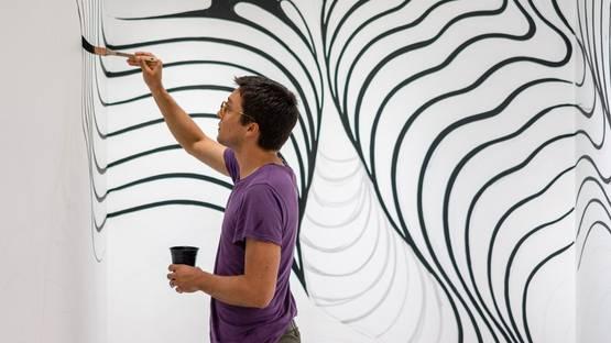 Brendan Monroe working on a wall - photo credits Brandon Shigeta, image courtesy of POW!WOW!