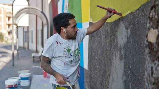 Elian working on a mural, photo credits Flavia Fiengo