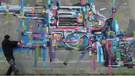 Steve Locatelli in front of his mural in Belgium