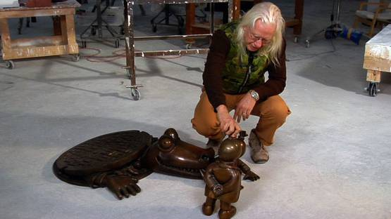Tom Otterness in studio with his bronze sculpture