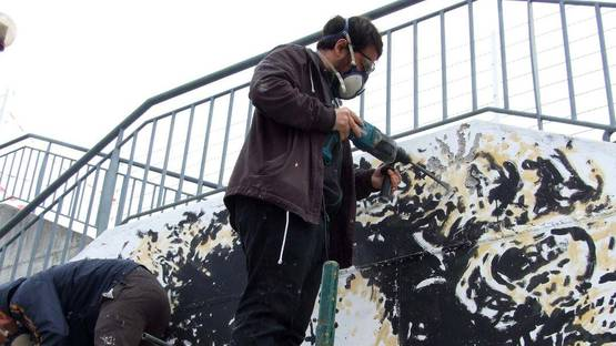 Vhils - Photo of the artist at work - Image via stick2target