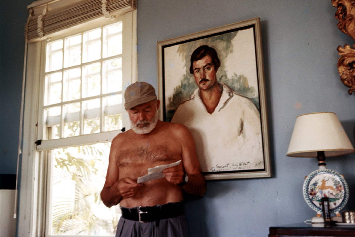 Ernest Hemingway at his home in Cuba, standing in front of the portrait of himself by Waldo Peirce titled Kid Balzac, 1929. Ernest Hemingway Collection, John F. Kennedy Presidential Library. Image via jfklibrary.org