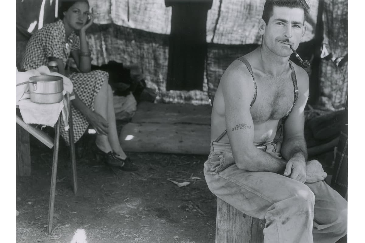 Dorothea Lange - Unemployed lumber worker goes with his wife to the bean harvest. Note social security number tattooed on his arm. Oregon, 1939