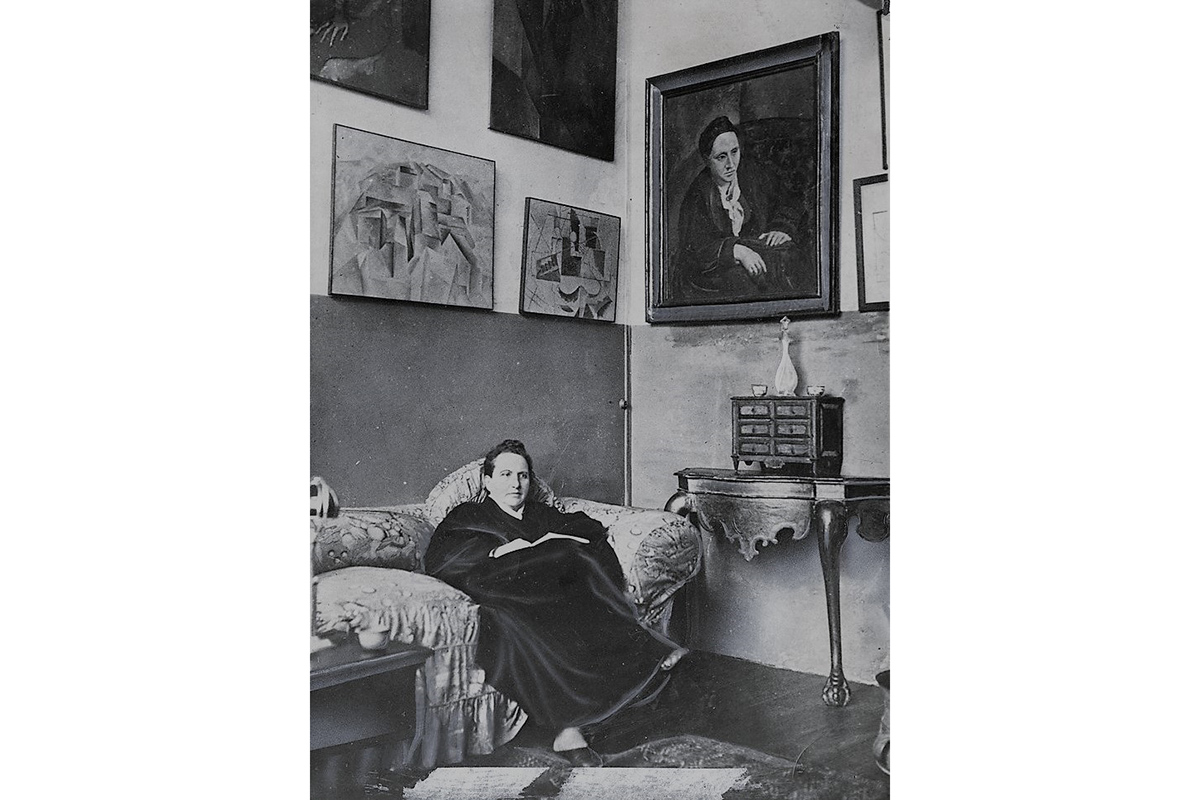 Gertrude Stein sitting on a sofa in her Paris studio, with a portrait of her by Pablo Picasso