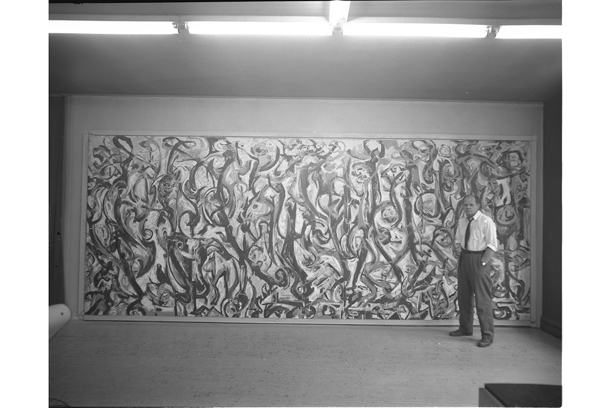 Jackson Pollock standing in front of Mural (1943) at the studios of Vogue magazine, ca. 1947