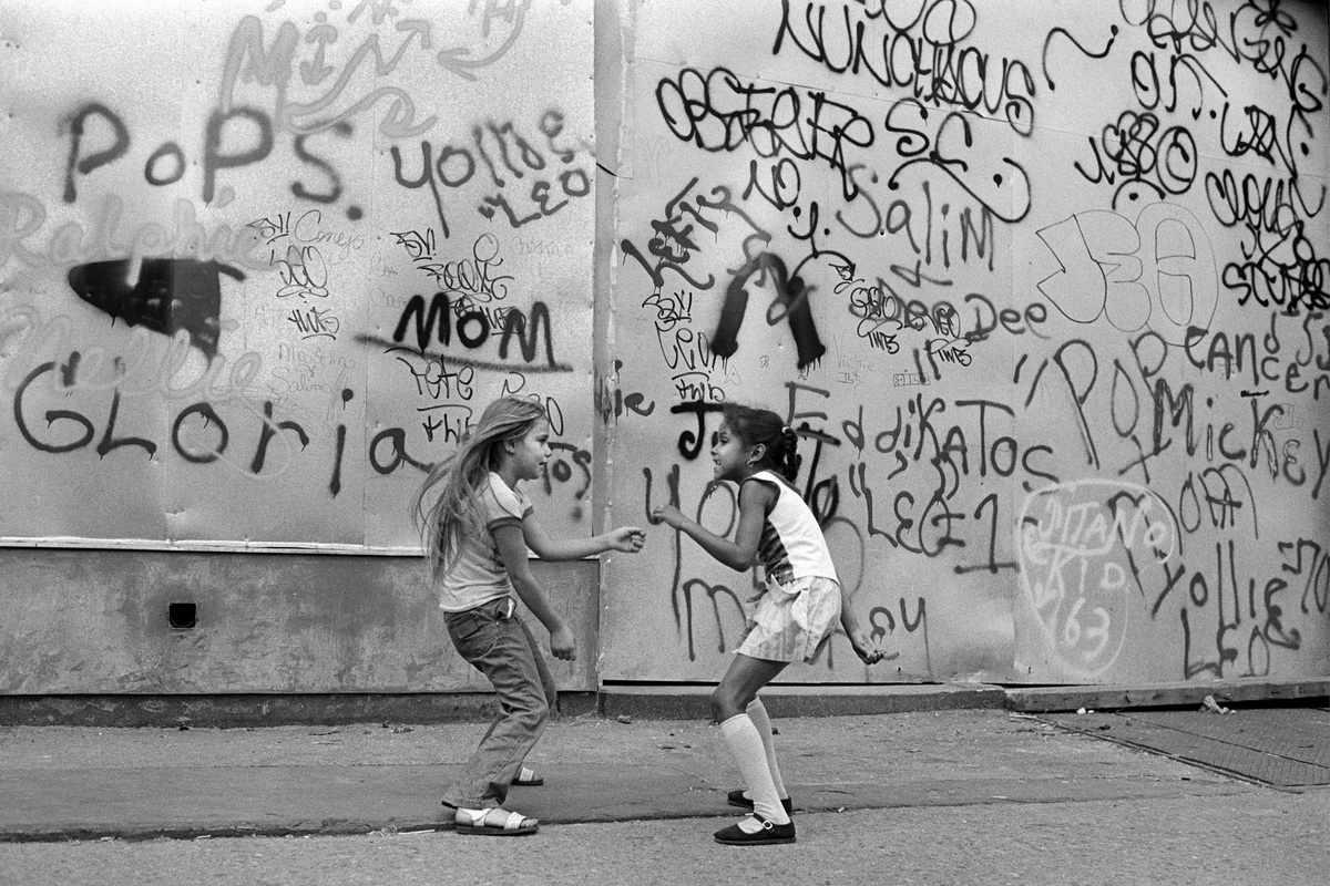 Martha Cooper - Girls Dancing to Disco Music from a Bar Against Graffiti Wall